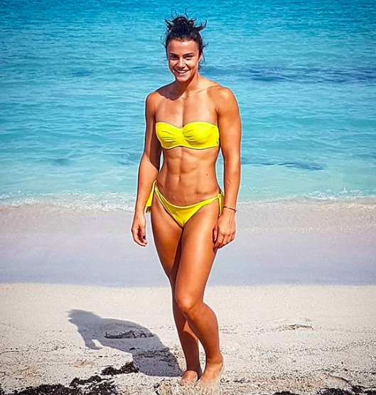 woman at beach in yellow swim suit shows off her muscular body